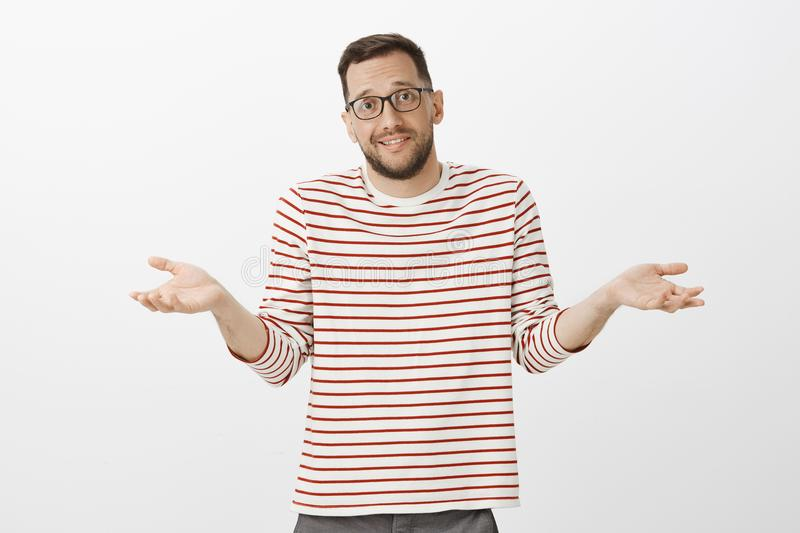 Portrait of clueless unaware handsome guy in glasses, shrugging with spread palms and awkward expression, being confused. And questioned, having no idea about royalty free stock images