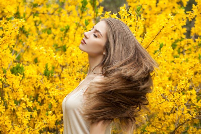 Portrait color? de belle femme dehors Fille gaie sur le fond de fleurs photos stock