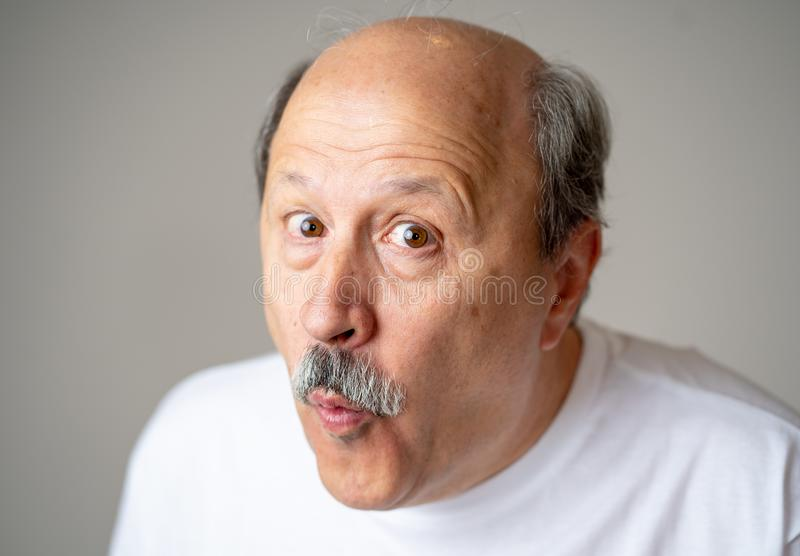 Portrait of comic and crazy senior man with funny face. Portrait of happy and cheerful senior mature man smiling and excited gesturing funny and comic in royalty free stock photography