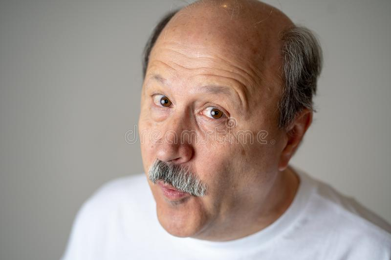 Portrait of comic and crazy senior man with funny face. Portrait of happy and cheerful senior mature man smiling and excited gesturing funny and comic in royalty free stock image