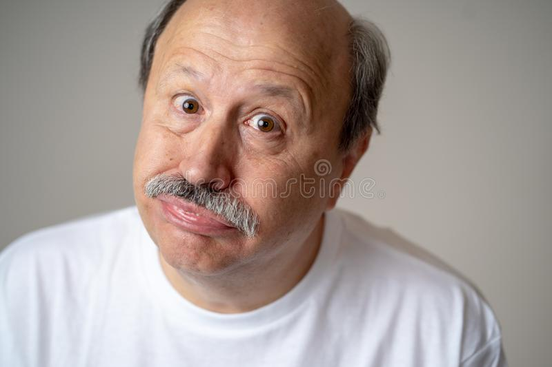 Portrait of comic and crazy senior man with funny face. Portrait of happy and cheerful senior mature man smiling and excited gesturing funny and comic in stock photo