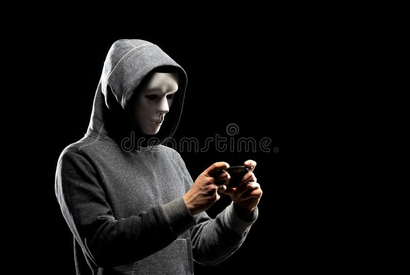 Computer hacker in white mask and hoodie. Obscured dark face. Data thief, internet fraud, darknet and cyber security. Portrait of computer hacker in white mask stock photo