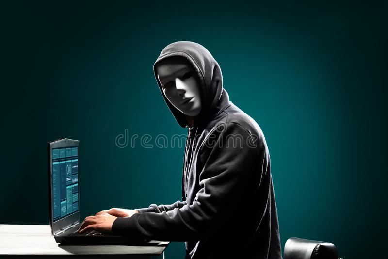 Computer hacker in white mask and hoodie. Obscured dark face. Data thief, internet fraud, darknet and cyber security. Portrait of computer hacker in white mask stock photos