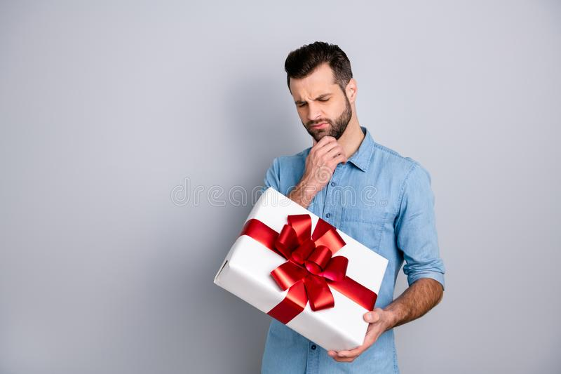 Portrait of concentrated bearded guy thinking reaction his sweetheart giftbox for 8-march touching chin by his fingers. Closing eyes wearing blue shirt isolated stock photo