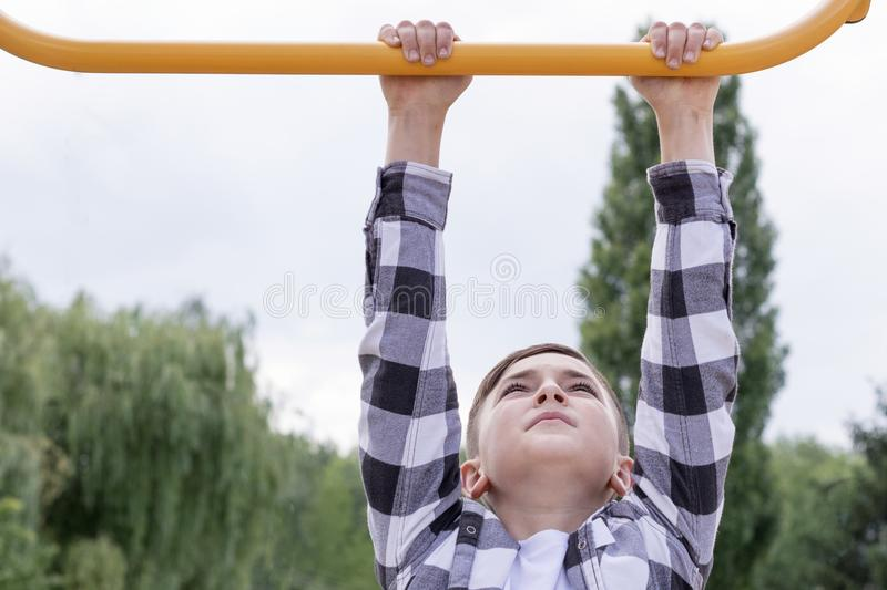 Teenager doing pull ups. Portrait of concentrated boy in plaid shirt doing exercise on horizontal bar outdoors. Healthy lifestyle concept. Blurred background royalty free stock photo