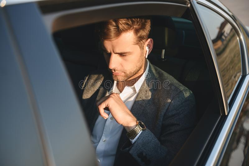 Portrait of concentrated caucasian man wearing businesslike suit. And earpod back sitting while riding in car stock photo