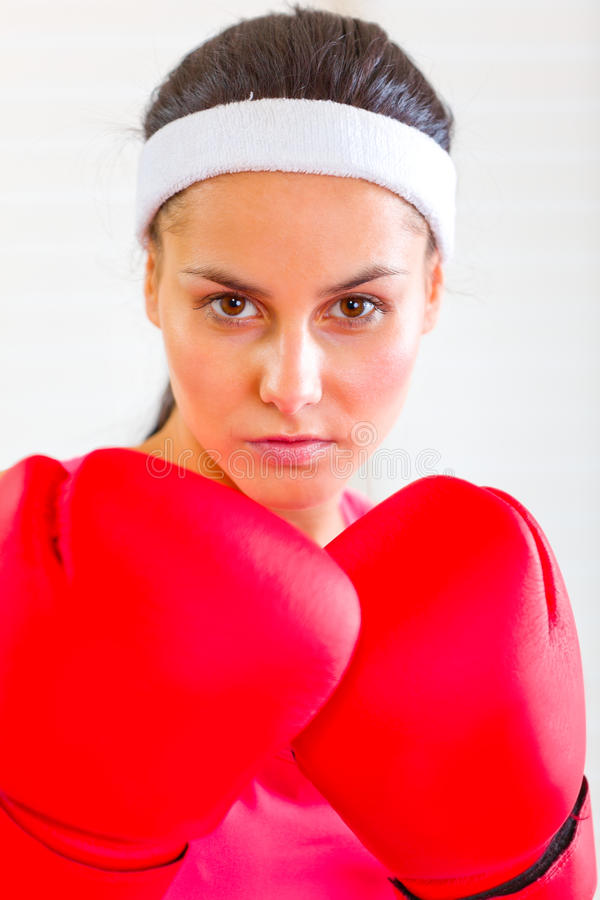 Portrait of concentrated fit girl in boxing gloves