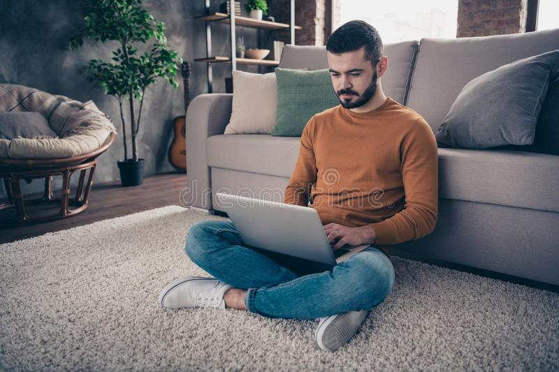 Portrait of concentrated focused man youth sit lotus position look read data statistics management denim jeans orange royalty free stock image