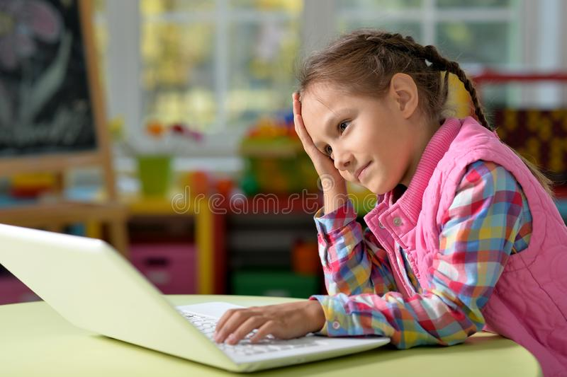 Portrait of concentrated little girl with laptop. Concentrated beautiful little girl with laptop at home stock photos