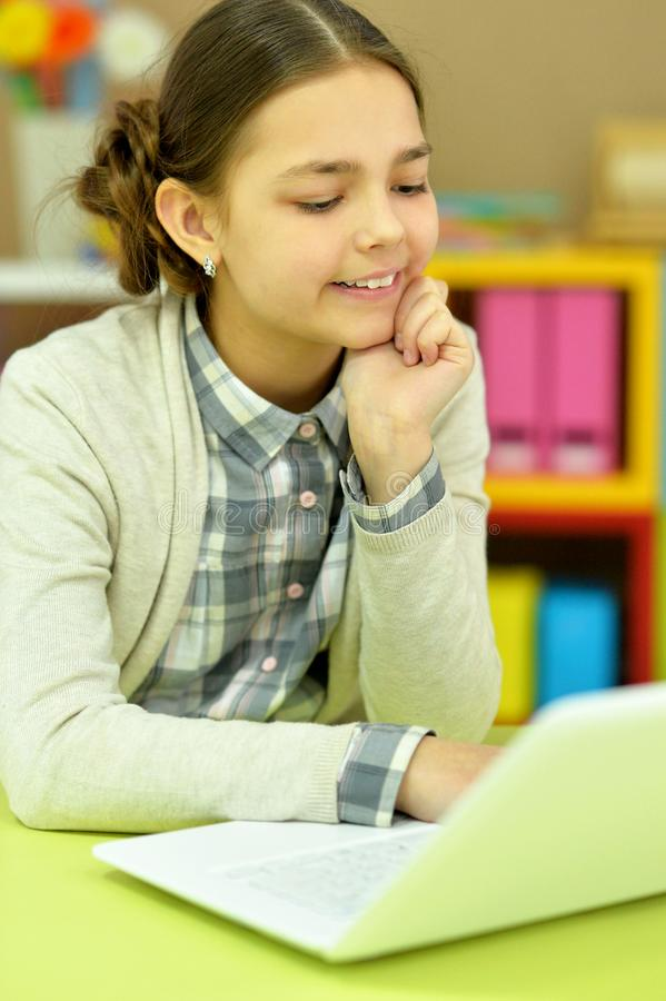 Portrait of concentrated little girl with laptop studying. At home royalty free stock image
