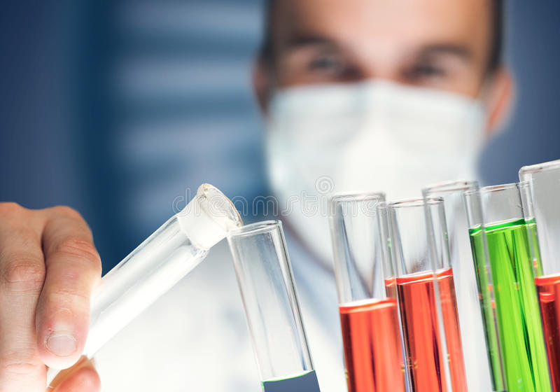 Portrait of concentrated male scientist working with reagents in laboratory. Young scientist mixing reagents in glass flask in clinical laboratory stock images
