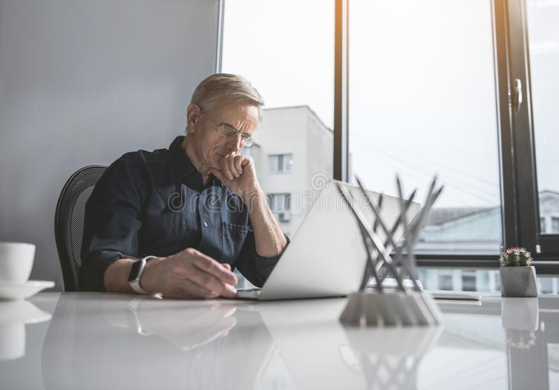 Focused senior male working with gadget. Portrait of concentrated old businessman looking at laptop while sitting at table in office. Abstracted worker during royalty free stock photography