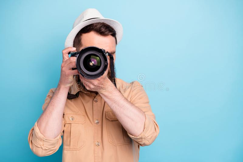 Portrait of concentrated person making photo looking wearing brown shirt  over blue background royalty free stock images