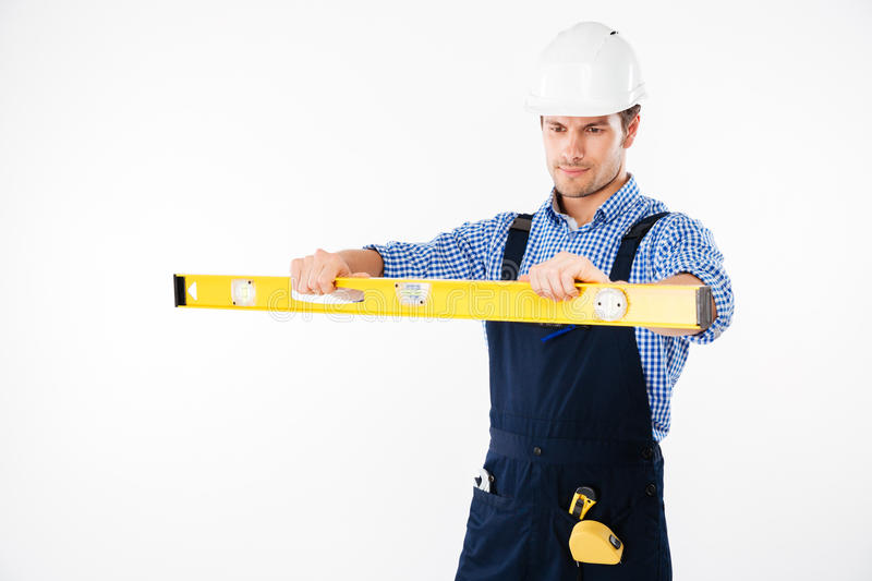 Portrait of a concentrated worker in overalls using level tool royalty free stock image