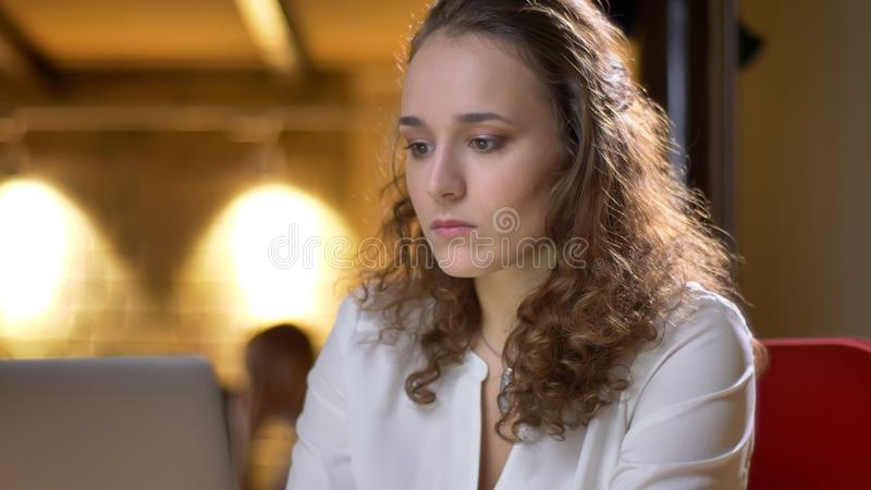 Portrait of concentrated young businesswoman watching into laptop on office background. Portrait of concentrated young businesswoman watching into laptop on stock images