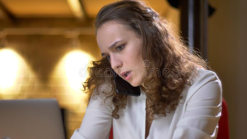 Portrait of concentrated young businesswoman working with laptop and talking on cellphone on office background. Portrait of concentrated young businesswoman stock photos