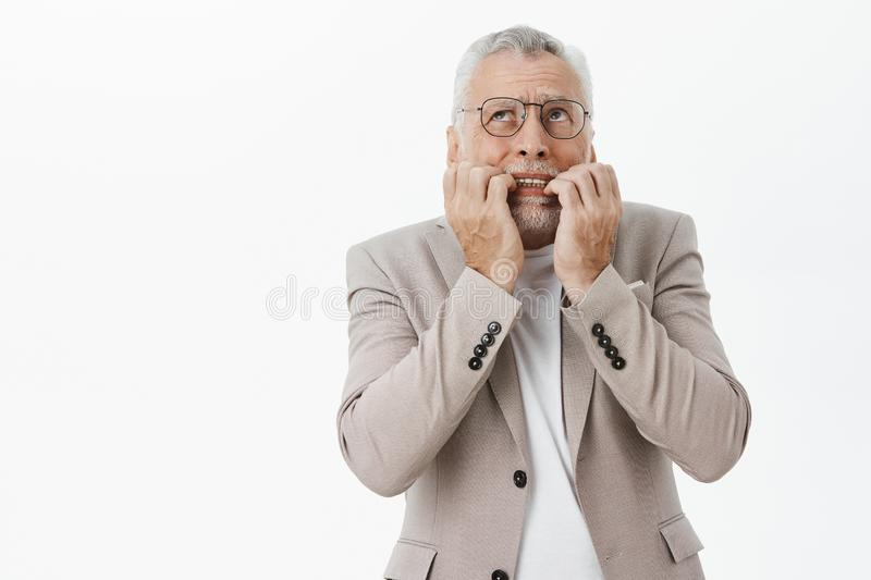 Portrait of concerned panicking and worried senior bearded man in glasses and suit biting fingers from nervousness and stock image