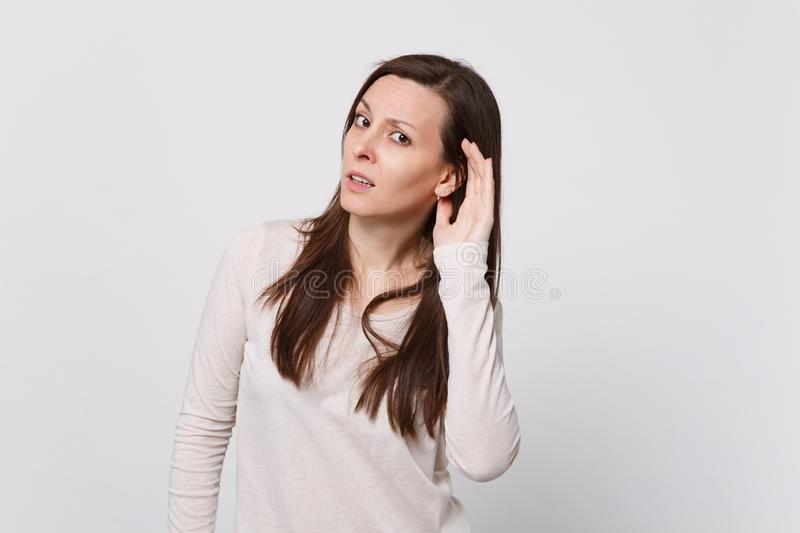 Portrait of concerned young woman in light clothes looking camera and eavesdrop with hearing gesture on white. Wall background. People sincere emotions royalty free stock photos