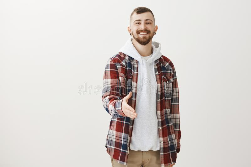 Portrait of confdent friendly-looking nice man with beard and stylish haircut, pulling hand towards camera and smiling royalty free stock images