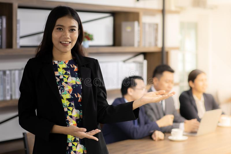 Portrait of Confidense Businesswoman. Portrait of confidence Businesswoman stand in front of table in meeting room in cafe with business team in background using royalty free stock photography