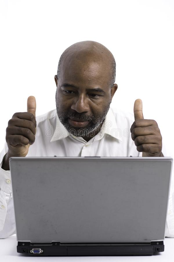 Portrait of a confident African American software expert signaling ok with thumbs up while sitting front of a laptop computer. stock photography