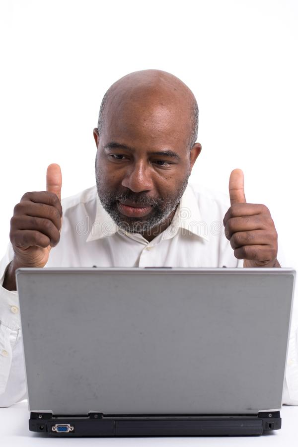 Portrait of a confident African American software expert signaling ok with thumbs up while sitting front of a laptop computer. stock photo