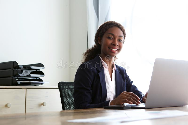 Confident african businesswoman sitting at desk with laptop. Portrait of confident african businesswoman sitting at desk with laptop stock image