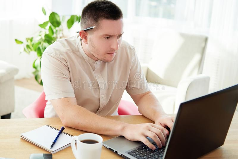 Portrait of confident businessman sitting at wood desk and typing on laptop computer in modern office, copy space royalty free stock photos