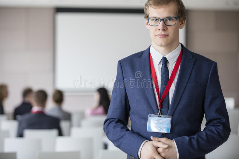 Portrait of confident businessman standing at seminar hall with colleagues sitting in background royalty free stock photo