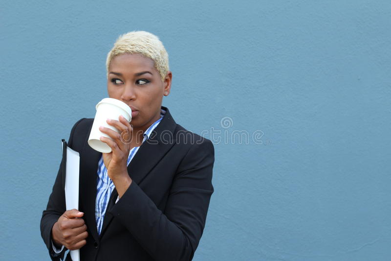 Portrait of a confident businesswoman drinking coffee outdoors and observing something that is happening. Gossiping concept stock photography