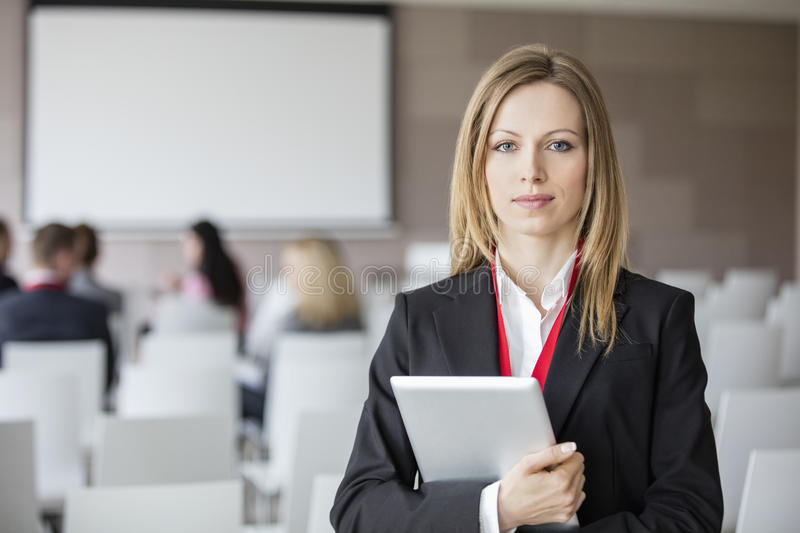 Portrait of confident businesswoman holding digital tablet in seminar hall royalty free stock images
