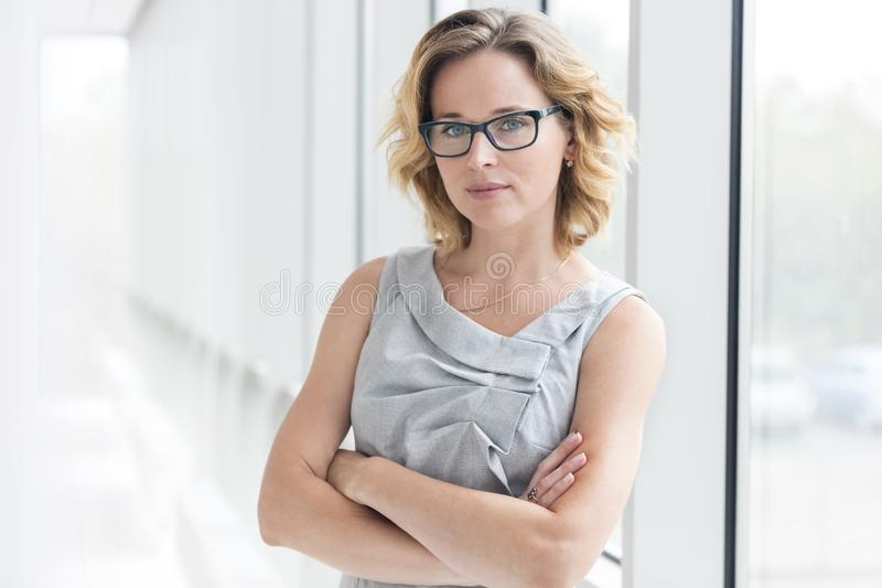 Portrait of confident businesswoman standing with arms crossed at new office royalty free stock photos
