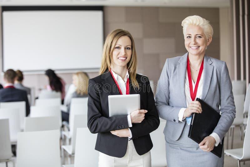 Portrait of confident businesswomen standing in seminar hall stock images