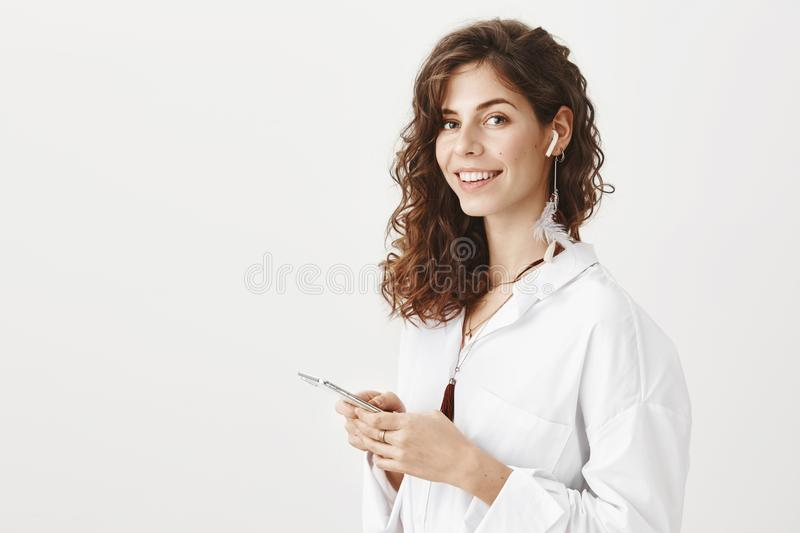 Portrait of confident charming successful woman holding smartphone in hands and wireless earphone in ear, standing half. Turned in trendy blouse, smiling and royalty free stock image