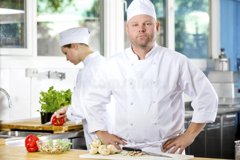 Portrait of confident chef making food in large kitchen. Portrait of a professional male chef standing in the large kitchen. Female assistant or chef working in stock photography