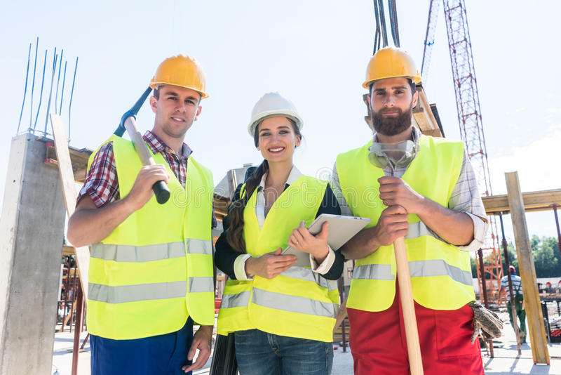 Portrait of confident colleagues posing during work break on construction site royalty free stock images
