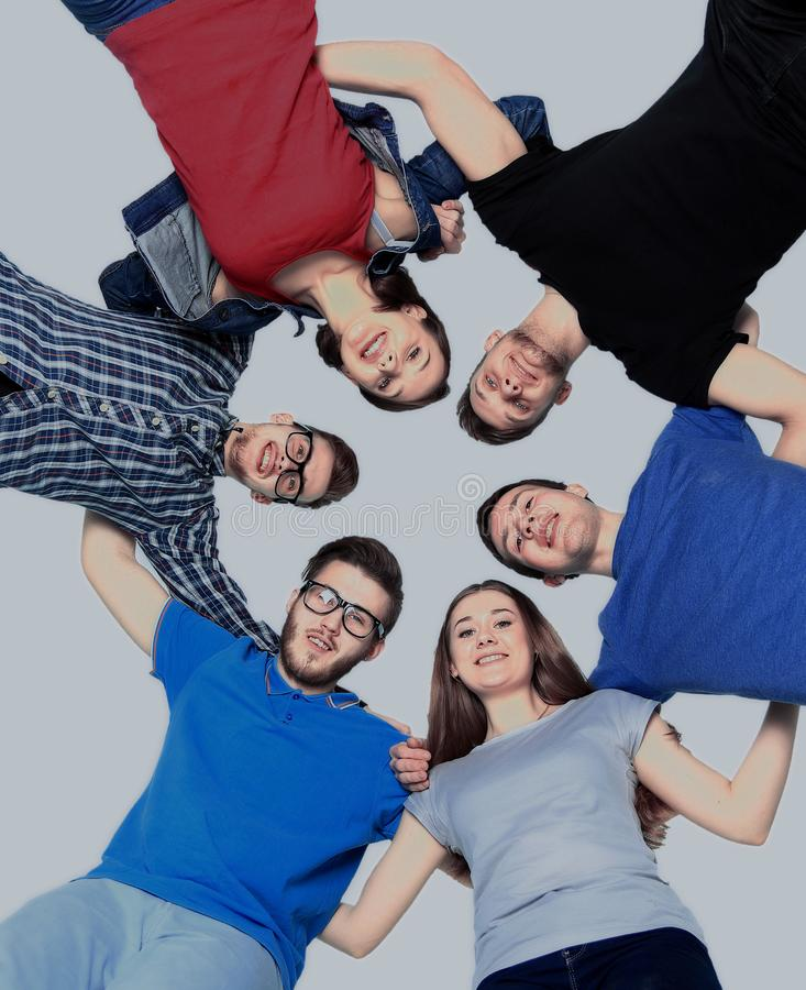Confident college students forming huddle over white background royalty free stock photo