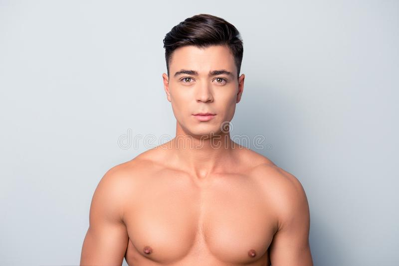 Portrait of confident concentrated handsome muscular with perfect ideal skin shaven guy, isolated on grey background royalty free stock photo