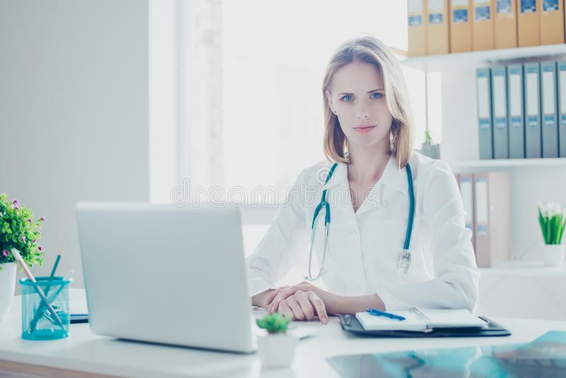 Portrait of confident concentrated medico wearing white coat, sh. E is sitting in front of her computer, at the workplace stock image