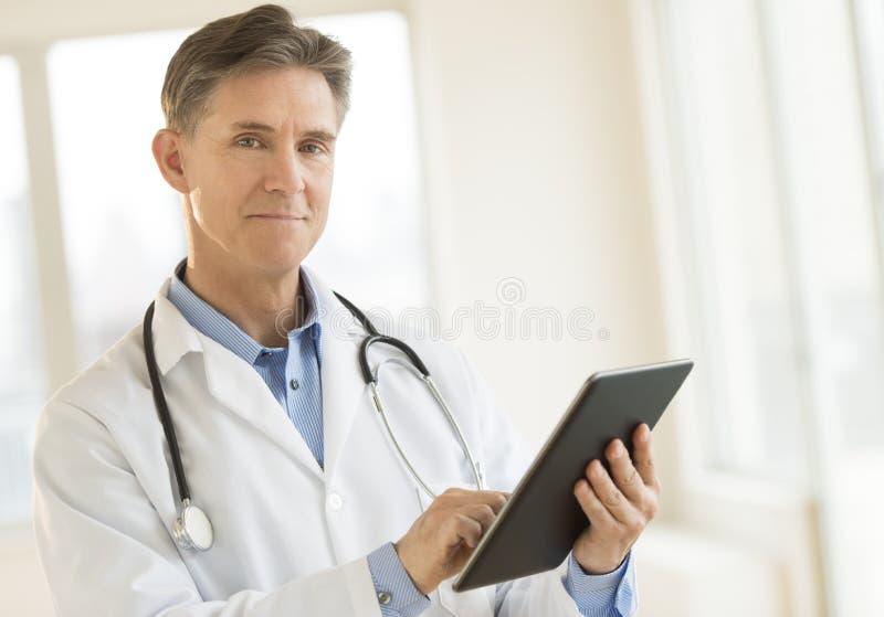 Portrait Of Confident Doctor Holding Digital Tablet stock image
