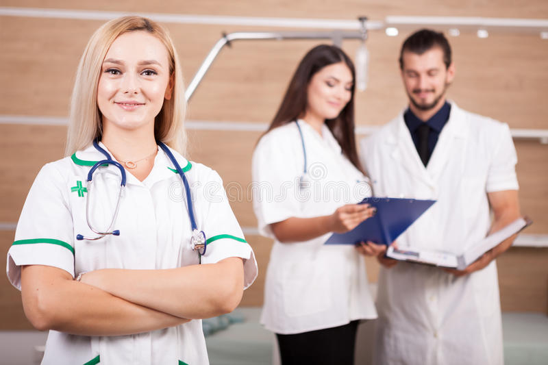 Portrait of confident doctor medical team with a blonde medic in. Front in hospital room royalty free stock image