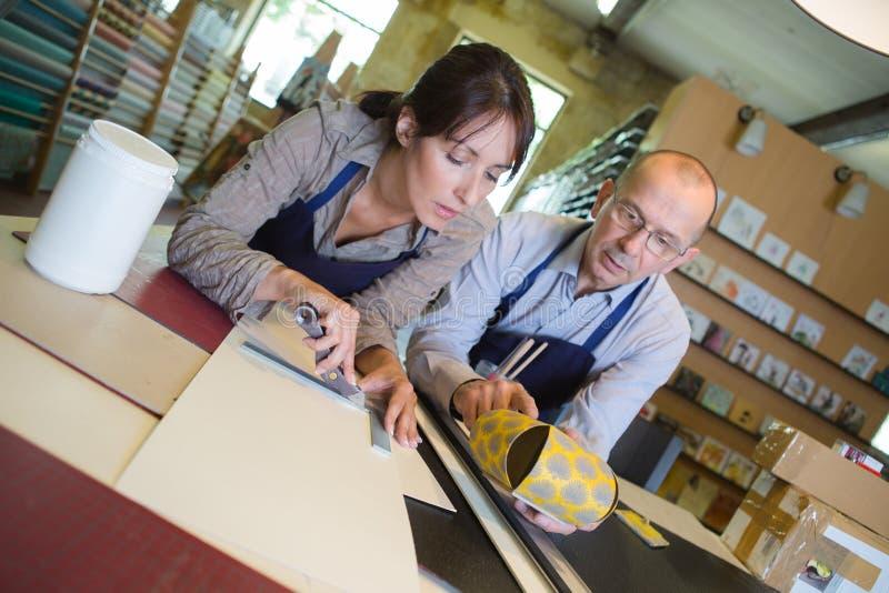 Portrait confident female carpenter measuring drawer in workshop stock image