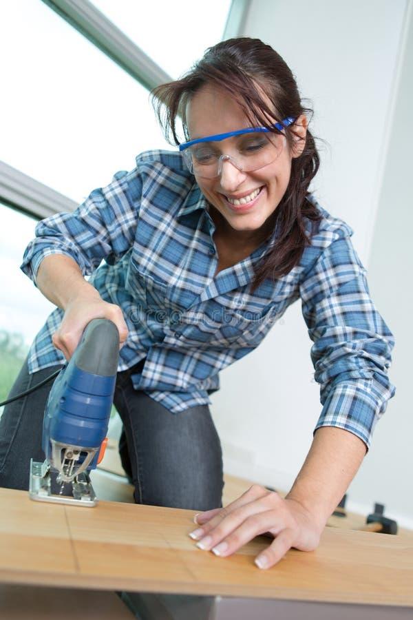Portrait confident female carpenter using bandsaw royalty free stock image
