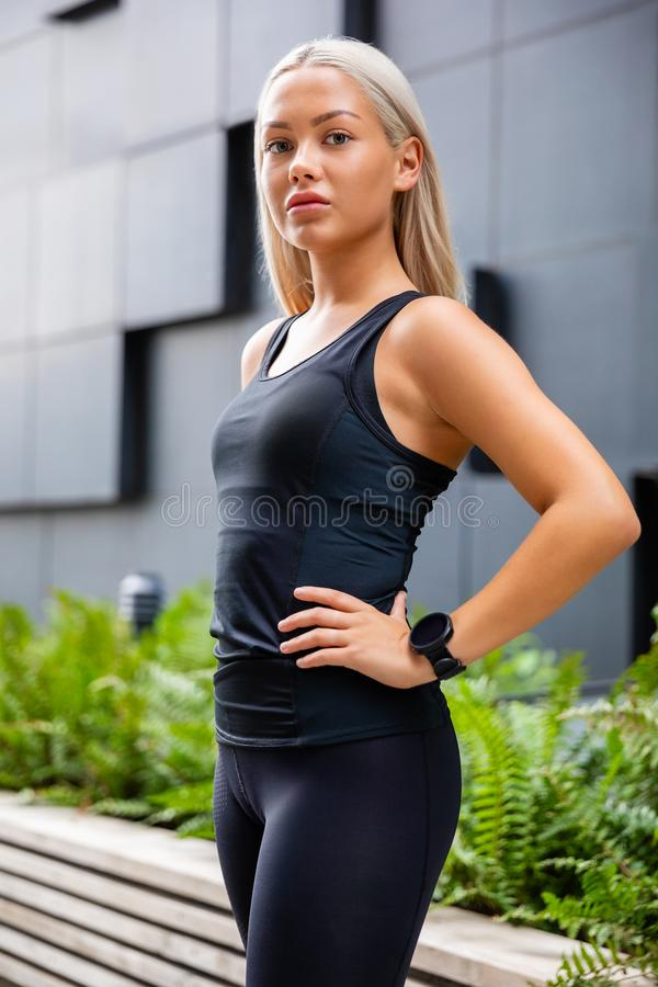 Confident Female Urban Jogger Standing With Hand On Waist royalty free stock photo