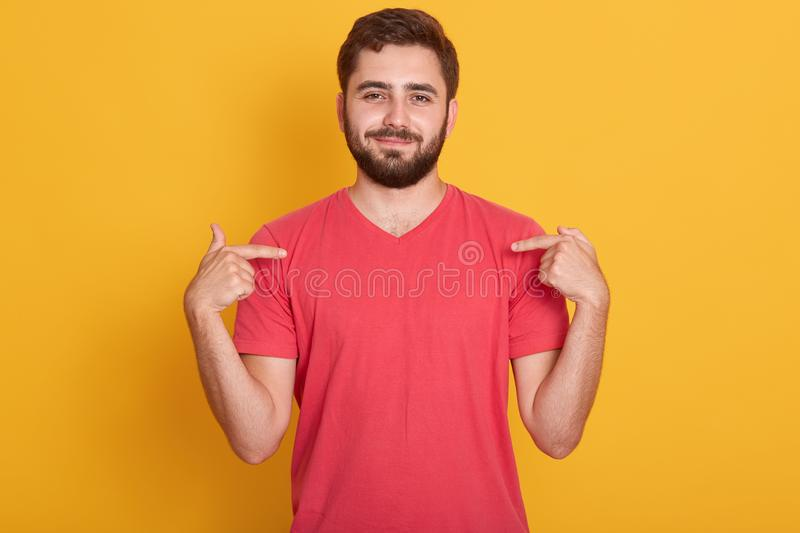 Portrait of confident good looking caucasian man wearing red casual t shirt, standing over yellow background, pointing on his t stock photos