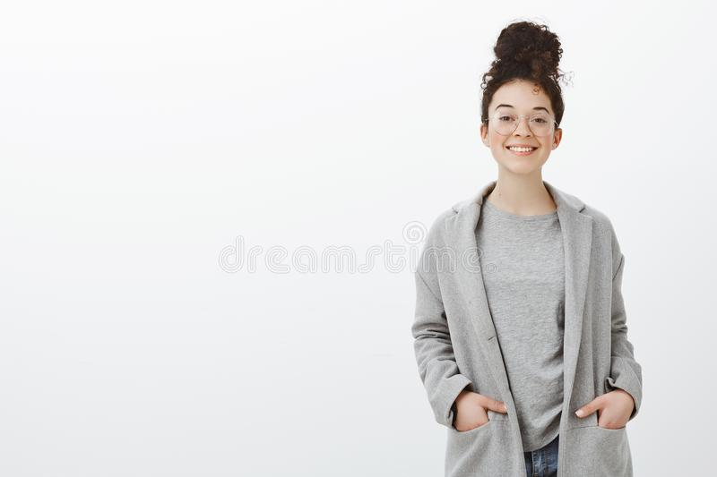 Portrait of confident happy good-looking girl with curly hair combed in bun, wearing gray coat and glasses, holding royalty free stock image