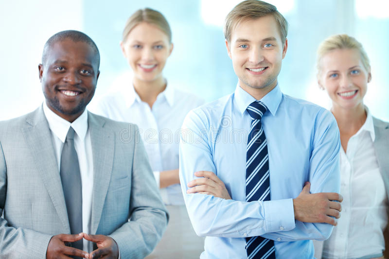 Male leader. Portrait of confident leader looking at camera with three partners behind stock photography