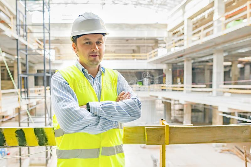 Portrait of confident male builder, manager, engineer with folded hands on construction site. Building, development concept.  stock photos