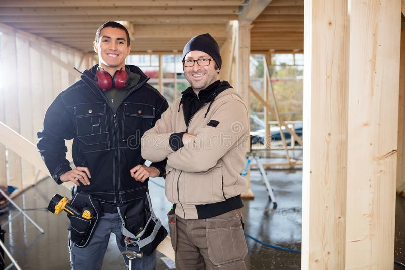 Confident Male Carpenters Standing At Construction Site stock photos
