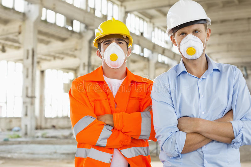 Portrait of confident male construction workers in protective workwear at site royalty free stock images